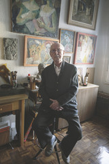 Old man sitting on his studio of painting and sculpture.