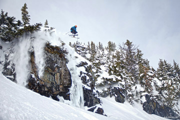 Skier jumping cliff in Whistler backcountry. Extreme ski