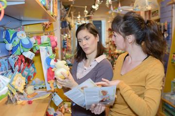 portrait of 2 women near souvenirs shelves in store