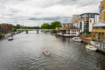 View of the river Thames with small boat passing and riverside apartments at Kingston-upon-Thames, a suburb of London, England, UK Wall mural