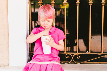 young girl with pink hair drinking from a straw