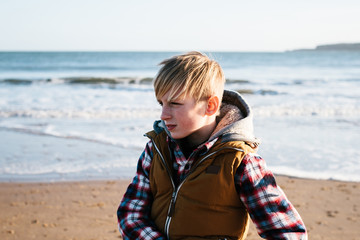 A teenage boy on a beach, looking away from camera.