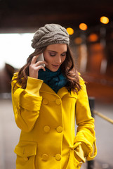 Woman in a Yellow Coat Talking on the Phone