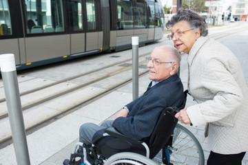 elderly lady pushing husband in wheelchair towards tram