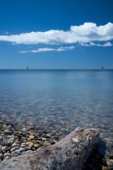 Stick on pebble beach under a cloudy blue sky