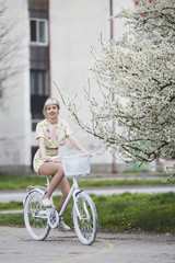 Beautiful young woman riding a bike in the city