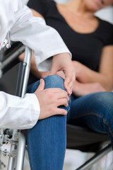 female handicapped suffers pain in her knee doctor ausculting