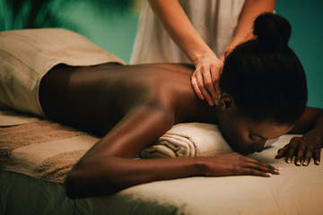 Woman receiving neck massage at spa