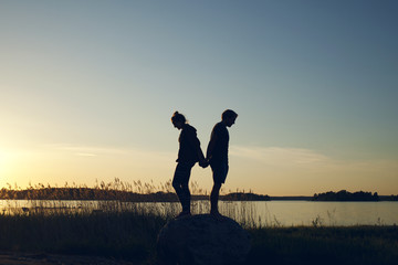 A couple enjoying the sunset around a lakeside on a warm summer night