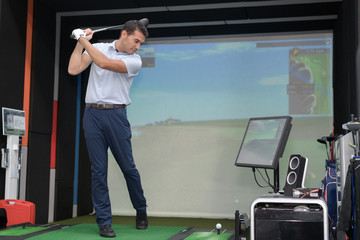 Man practicing golf swing using simulator