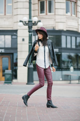 A trendy girl dressed in leather walking and looking back