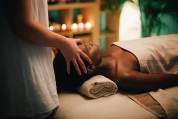 Woman receiving head massage at spa