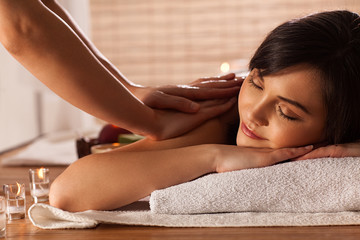 Woman enjoying massage in spa center.