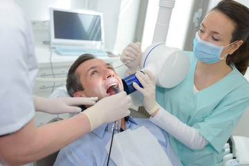 patient in a dentists panoramic and cephalometric x-ray system