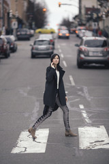 A well dressed woman crossing the street