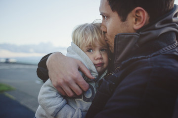 Father holds and cuddles daughter on cold winter day