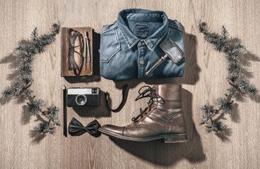The objects of a hipster man in order on a wood background.