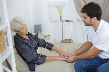 male carer holding old ladys hand