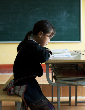 Young girl from Hmong tribe, studying alone in classroom. Sapa.