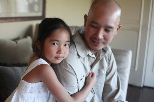 Asian daughter hugging father while making direct eye contact with camera