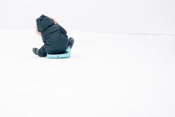 A little boy sledding down a hill in a snowsuit.