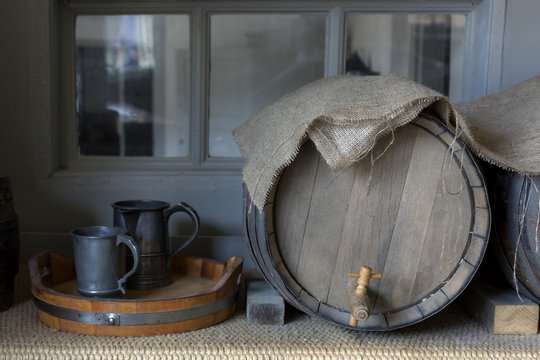 Close-up of beer barrels and pewter mugs covered with hessian cloth