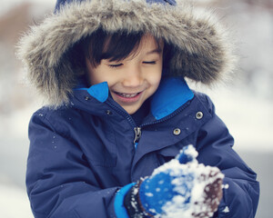 A young child makes a snowball