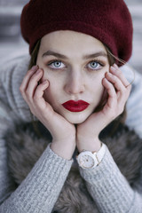 Young beautiful woman with red hat, blue eyes and freckles