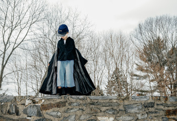 Boy pretending to be a Union soldier marches on a tall stone wall