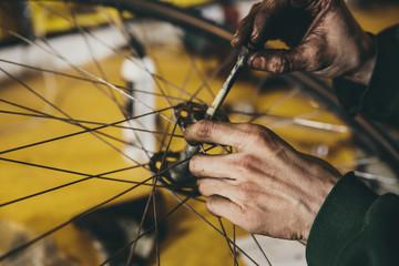 Mechanics hands placing an axle into a wheel hub