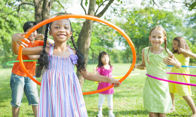 Cute diverse kids playing with hula hoops