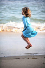 Girl jumping on the beach wearing blue dress