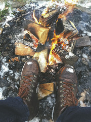 Low section of a man wearing boots standing near campfire