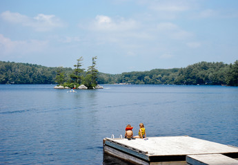Kids sit on a dock on a lake in summer