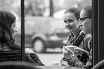 Woman sipping her coffee with friends at a street cafe