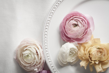 Table setting with plate and pastel colored ranunculus flowers