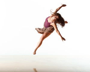 Female dancer leaping with arms outstretched