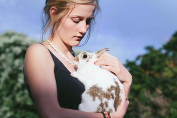 Girl holding a white pet rabbit