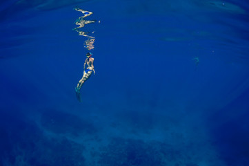 Free diving in calm blue ocean