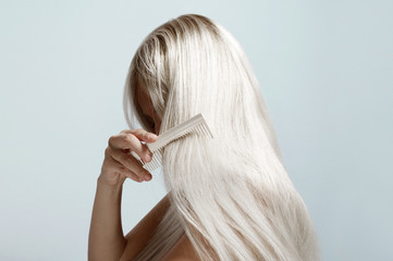 woman combing long blond hair