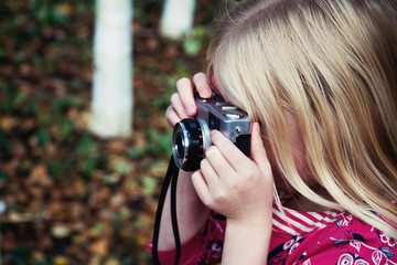 A little girl taking photographs with a vintage camera