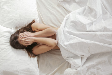 Woman covered her face with hands in a white bed.