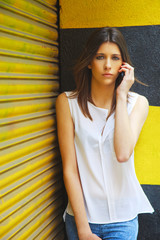 Young woman with her mobile phone standing in front of yellow shutter door.