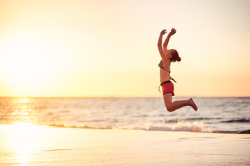 Girl leaping at the beach at sunset