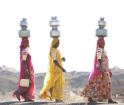 Women carrying water jugs on their heads