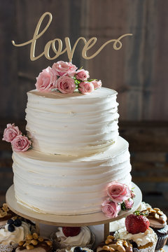 Rustic ruffled wedding cake with love topper and fresh pink roses