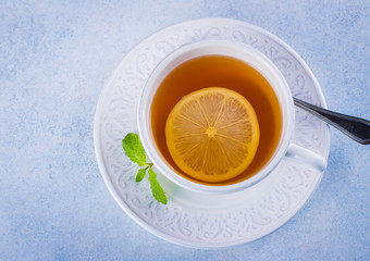 Cup of hot lemon tea with mint on blue stone table background. Healthy drink cold. Copy space. Winter drink