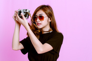 Fashion photo of young girl taking picture with camera on pink background
