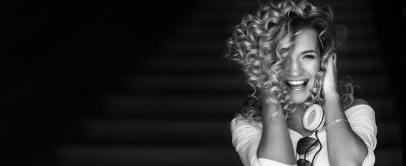 Portrait of a curly girl in headphones. She listens to music and dances. Black and white photo.