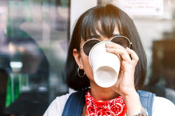 Woman holding cup of coffee in coffee shop